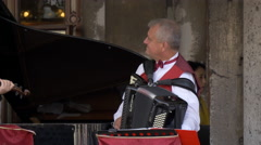 Man playing an accordion on the street in Venice Stock Footage