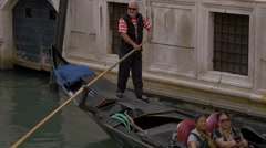 Old man paddling a gondola and smiling in Venice Stock Footage