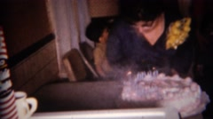 1959: Lady blows out birthday cake with many smoking candles. BUFFALO, NEW YORK Stock Footage