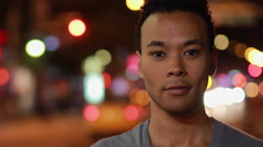 Young man smiling happy face portrait in city at night - stock footage