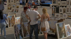 Buying paintings on the street in Venice Stock Footage