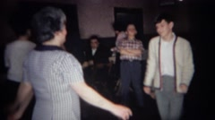 1966: Teenager dances with grandma around smoke filled reception hall. BUFFALO, Stock Footage