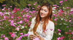 Beautiful woman with the cosmos flower field Stock Footage