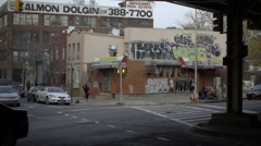 cars driving, people walking and graffiti on building gritty panning Brooklyn NY - stock footage