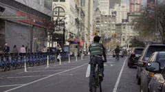 Delivery boy bicyclist with plastic bag of food pedaling street Union Square NYC Stock Footage