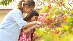 Happy Asian girl watering her flower in the garden with mother Stock Footage