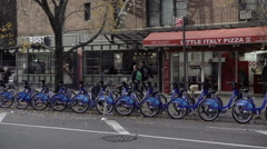 Panning across Citi Bikes parked docking station Little Italy Pizza pizzeria NYC Stock Footage