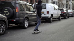 Skateboarder riding down Brooklyn street skateboard slow motion USPS truck NYC Stock Footage