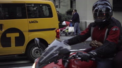 woman holding onto man on motorcycle making turn onto 5th Avenue in evening NYC - stock footage