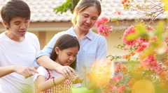 Happy Asian girl watering her flower in the garden with parents - stock footage