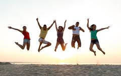Smiling friends dancing and jumping on beach Stock Photos