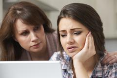 Mother Comforting Daughter Victimized By Online Bullying - stock photo