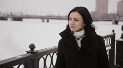 Beautiful woman walking on a frozen winter river bridge Stock Footage