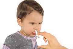 parent's hand of a girl applies a nasal spray - stock photo
