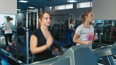 Two women running on the treadmill in the gym Stock Footage