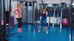 Trainer shows the visitor exercises on fitness equipment Stock Footage