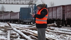 Railway officer talking on the smartphone near freight wagons Stock Footage
