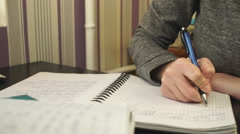 The student writes in a notebook Stock Footage