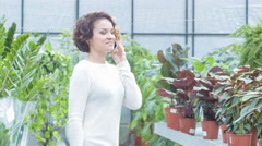 Young woman having a phone talk in the greenhouse - stock footage