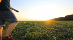 Young boy walking with his father in a grassy field ins slowmotion Stock Footage