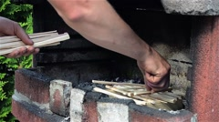 Man arranges wood oven grill to give them fire and prepare the food Stock Footage