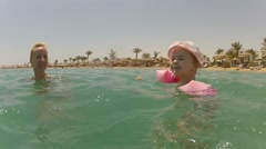 Mom with little daughter funny swim in resort bay sea water Time Lapse Stock Footage