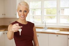 Stock Photo of Young Woman Holding Keys To New Home