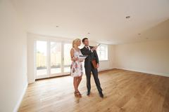 Estate Agent Showing Young Woman Around New Empty Property - stock photo