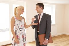 Estate Agent Handing Over Keys Of New Home To Female Buyer - stock photo