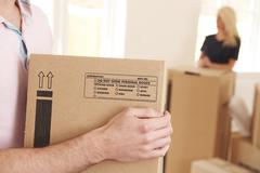 Close Of Man Carrying Box Into New Home - stock photo
