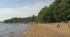 People relaxing on a beach near the forest at Killbear Provincial Park - stock footage