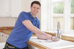 Plumber Fixing Kitchen Tap With Adjustable Wrench Stock Photos