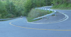 Black car driving on curves on a road near the forest at  Caledon, Canada Stock Footage