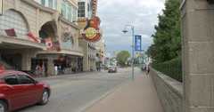 People walking and cars driving by Hard Rock Cafe at Niagara Falls, Canada Stock Footage