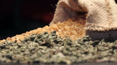 Brown sugar in gunny sack and a pile of dried green tea leaves, rotating - stock footage