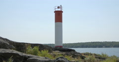 Stock Video Footage of View of a lighthouse and a boat sailing on the lake at Killbear Provincial Park