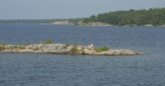 Couple relaxing on a lagoon of the lake at Killbear Provincial Park Stock Footage