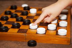 child's hand moves the piece to the chessboard - stock photo