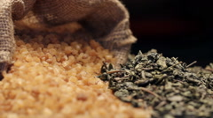 Brown sugar in gunny sack and a pile of dried green tea leaves, rotating Stock Footage