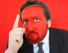 Young man portait with red painted face and copy space Stock Photos