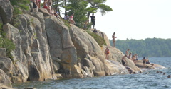 People standing, swimming and jumping in the lake at Killbear Provincial Park Stock Footage