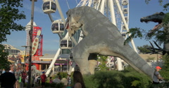 View of people near a big dinosaur and Niagara Skywheel at Niagara Falls, Canada Stock Footage