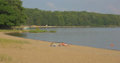 Two women tanning on the beach of the lake at Killbear Provincial Park - stock footage