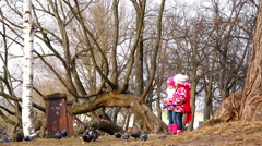 Two girls in a red jacket with interest feeding pigeons with bread in a park - stock footage