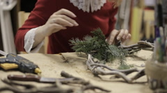 Stock Video Footage of girl decorates a Christmas wreath with cones