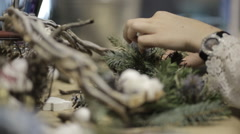 Girl in the studio preparing decorations for Christmas wreaths Stock Footage