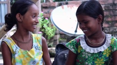 Two Indian village girls smile and play with a flower - stock footage