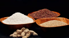 Red rice,millet grains,tapioca pearls in small bowls and a pile of peanuts Stock Footage