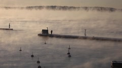 Ice-cold steaming sea, ice fisherman on the pier Stock Footage