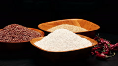 Red rice,millet grains,tapioca pearls in small bowls and a pile of dried chili Stock Footage
